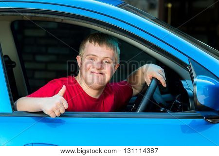 Close up portrait of young man with down syndrome sitting behind steering wheel in blue car.