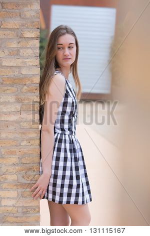 Fair-haired woman in checked dress leaning on wall and looking down