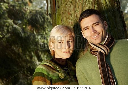 Portrait of young couple standing in park together in sunlight.?