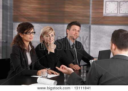 Panel of friendly businesspeople sitting at meeting table conducting job interview listening to applicant.?