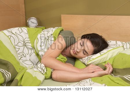 Mid-adult woman sleeping late in morning in bedroom.?