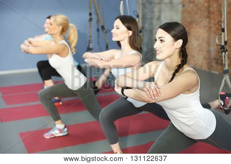 Attractive young girls are exercising in group. They are posing and stretching leg on the trx straps. The ladies are crossing arms and smiling
