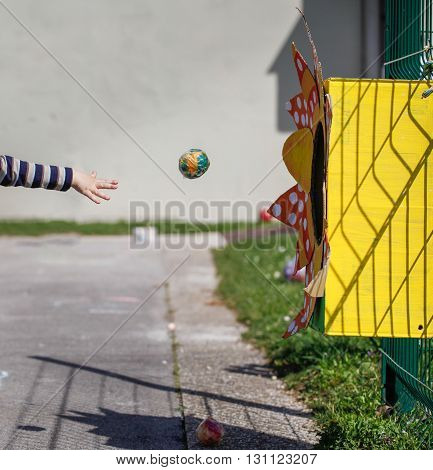 Child playing with homemade do-it-yourself educational throw and score ball toy in the playground. Learning through experience concept gross and fine motor skills educational approach concept.