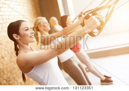 Cheerful fit girls are doing push-ups with trx fitness straps. They are standing and stretching arms. The ladies are smiling