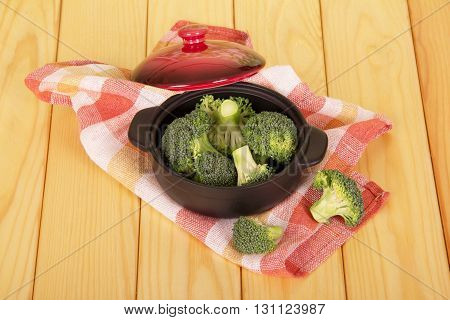 Fresh broccoli in a saucepan on a background of light wood.