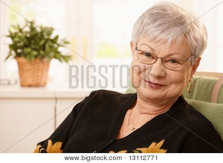 Portrait of smiling senior lady wearing glasses, looking at camera.?