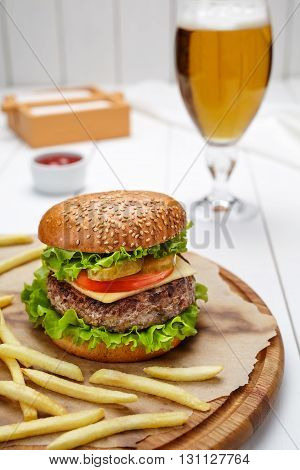 Hamburger with grilled marbled beef, tomato, cheese, salad and french fries traditional meat fast food with ketchup and beer. Restaurant burger menu meal.
