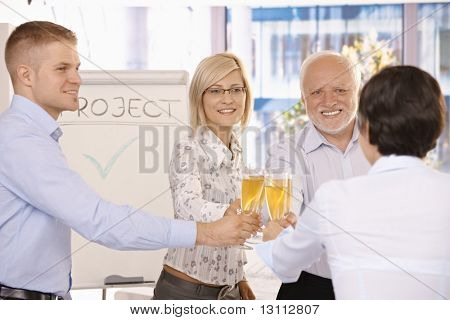 Smiling businessteam clinking champagne glasses, celebrating success in office.?