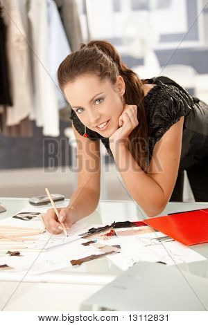 Young, attractive fashion designer working in office, drawing, leaning on desk, smiling.?