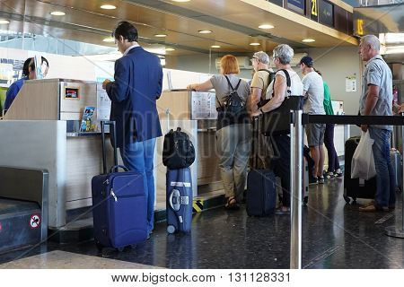 VALENCIA, SPAIN - MAY 21, 2016: Airline passengers checking in at an airline counter in the Valencia Airport. About 4.98 million passengers passed through the airport in 2015.