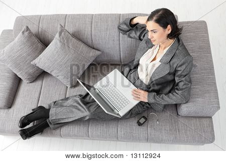 Young businesswoman sitting on sofa, working with laptop computer. Isolated on white background.?