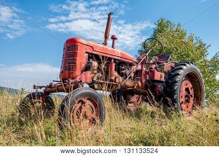 Old red rusty tractor in a field