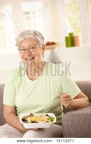 Happy senior woman eating healthy salad at home. Looking at camera, smiling.?