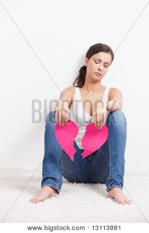 Attractive young girl sitting on floor lovelorn with pink heart in hands.?