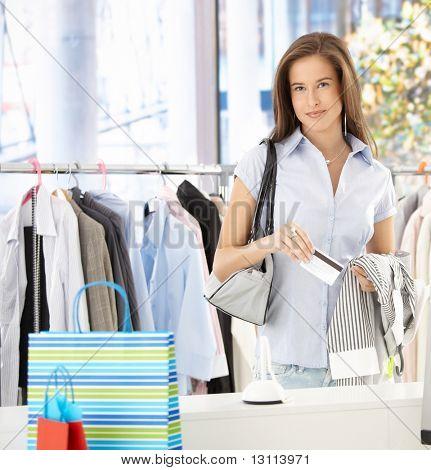 Frau stehend im Bekleidungsgeschäft, bezahlen mit Kreditkarte, lächelnd in die Kamera.?
