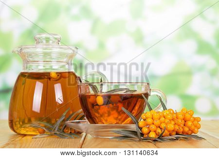 Drink the jug and cup of tea with sea-buckthorn berries on a green abstract background.