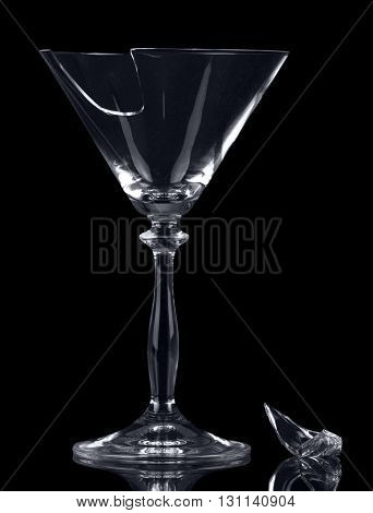 Broken glass martini glass and a fragment isolated on black background.