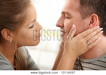 Mid-adult woman holding man's face in two hands, about to kiss with eyes closed, faces in closeup.