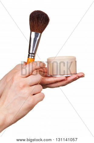 In female hands a cosmetic brush and face powder isolated on white background.