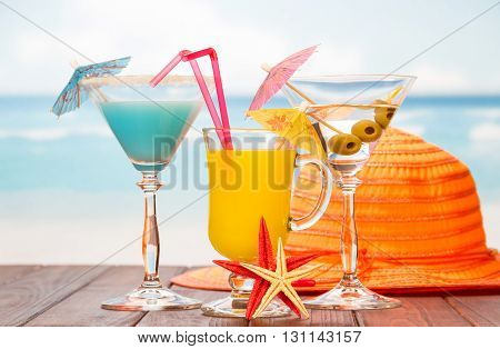 Cocktails, Juice, hat and starfish on a sea background.