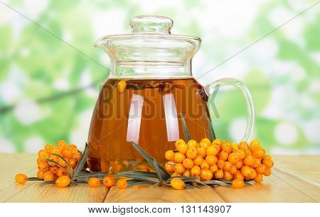 Drink pitcher of sea buckthorn berries on a green abstract background.