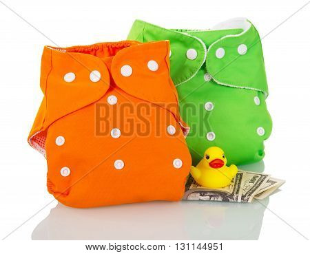 Modern cloth diapers, money, and a rubber duck isolated on white background.
