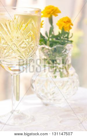 Elegant Crystal Goblet with White Wine with Marigold Flowers in the Background. Made in High Key Lighting