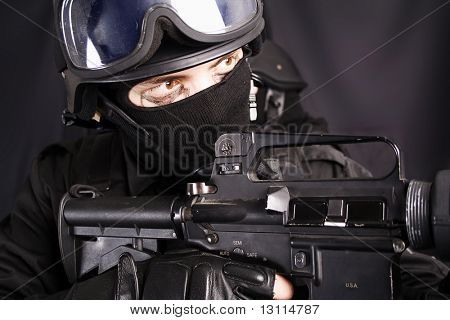 Shot of a soldier holding gun. Uniform conforms to special services(soldiers) of the NATO countries. Shot in studio. Isolated with clipping path.