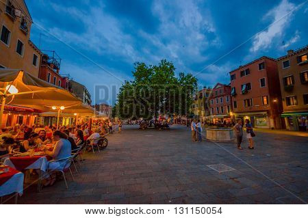 VENICE, ITALY - JUNE 18, 2015: Turists enjoying Venice at sunrise, nice square with restaurants and paths to walk.