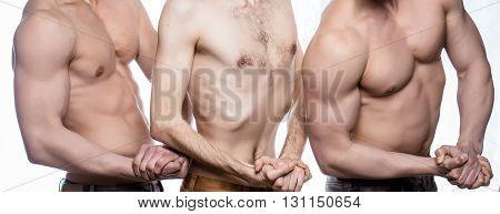 Slim man pose between two athletes with sporty muscular strong sexy body in studio isolated on white background