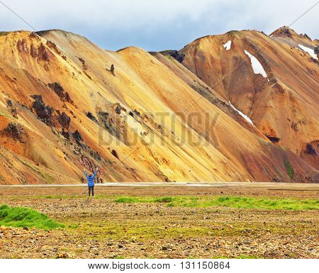 Pink and orange Mountains National Park Landmannalaugar in Iceland. At the foot of the mountains is worth admiring woman -turist. Snow remained on the mountains last year.