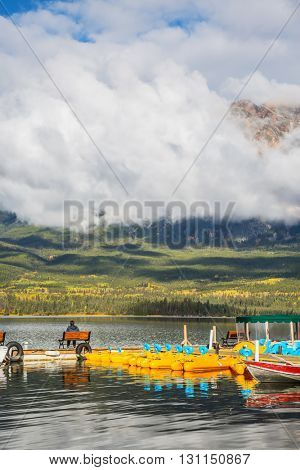 On a bench of the boat mooring sits middle-aged woman with camera. Cumulus clouds over the Pyramid mountain and Pyramid Lake
