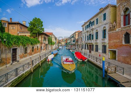 VENICE, ITALY - JUNE 18, 2015: Venice canal with various boats on the sides and unidentified men sailing a boat in the middle. Water transportation