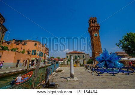MURANO, ITALY - JUNE 16, 2015: Nice view of Murano water canal, a little gondola passing and blue glass sculpture on the side with brick tower.