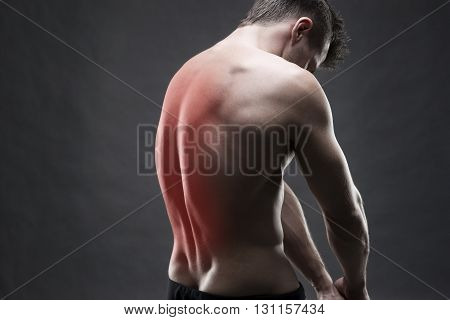 Man with backache. Pain in the human body. Muscular male body. Handsome bodybuilder posing on gray background with red dot