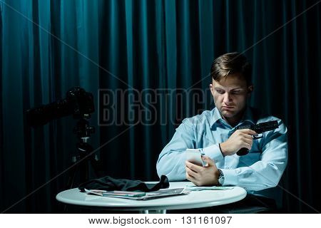 Serial killer sitting in dark interior beside small table holding gun and cellphone