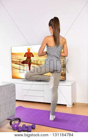 Yoga video fitness class - woman exercising training balance at home in living room watching tv following an online beach workout program streaming on smart television from web.