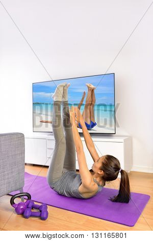 Home fitness ab workout in front of television. Girl doing toe touch crunch exercises to train upper abs for a flat stomach while watching a nature TV show or training program living a healthy life.