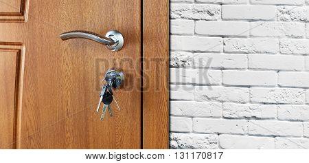 Closed door handle. Door lock with keys. Brown wooden door closeup at white brick wall. Modern interior design, door handle. New house concept. Real estate.