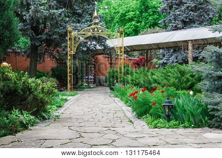 Beautiful landscape design, garden path with stone tiles, evergreen bushes, fir trees, blue spruces and shrubs in sunlight. Modern landscaping near castle, metal arch. Summer garden or park design.