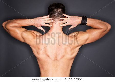Torso of a man's well shaped trapezius - isolated on black.