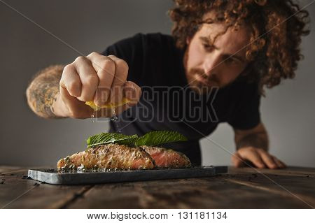 Man Cooks Healthy Meal, Squeezes Limon On Two Raw Pieces Of Salmon Decorated With Mint Leaf In White
