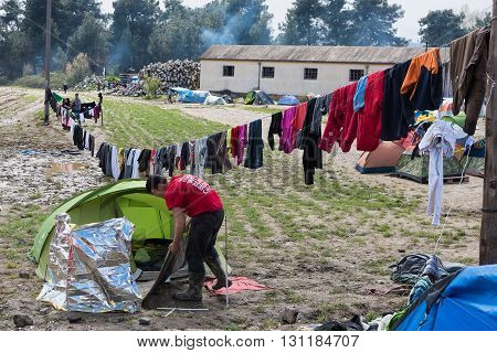 IDOMENI, GREECE - MARCH 17, 2015: A refugee from Syria cleans his tent after heavy rain on March 17  2015 in the refugee camp of Idomeni  Greece. For several weeks more than 10.000 refugees and immigrants wait here for the borders to open.