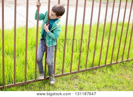illegally entering. child crawls through the bars of the iron fence