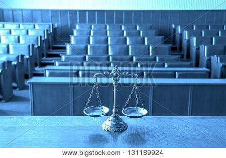Symbol of law and justice in the empty courtroom focus on the scales BLUE TONE