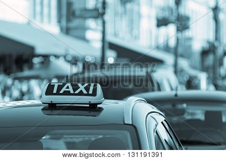 symbol or sign with an inscription of a taxi is located on a car roof on an indistinct background city of blue color