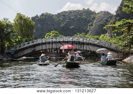 View of the bridge over the famous Ngo Dong river while boat ride in Tam Coc. Tourist boats are seen on the river. Tom Coc comprises of 3 popular caves and Bich Dong pagoda.
