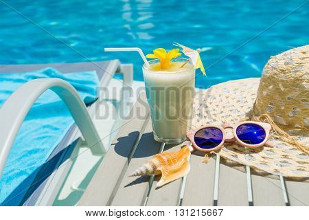Swimming pool table with sunglasses, hat and fresh cocktail - Selective focus