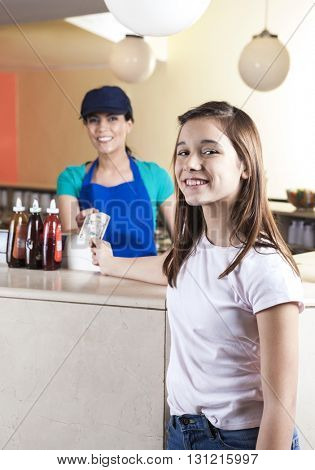 Smiling Girl Giving Note To Waitress In Ice Cream Parlor