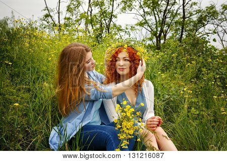 Best friends forever. Girlfriends talking in the park. BFF. She wears a wreath of wild flowers on the head of a friend.
